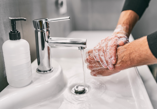 A person thoroughly washing their hands with soap