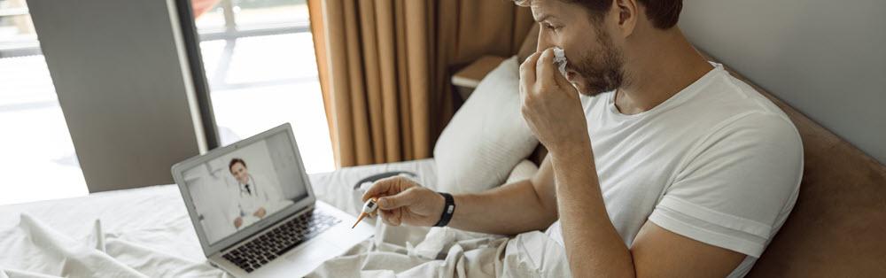 hombre enfermo en cama con un pañuelo desechable y un termómetro