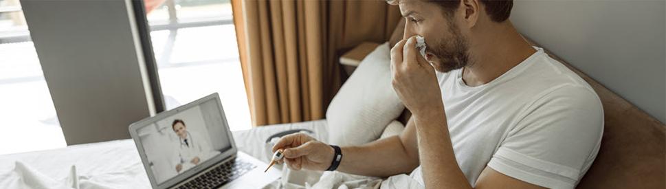hombre enfermo en la cama haciendo una consulta a través de telesalud