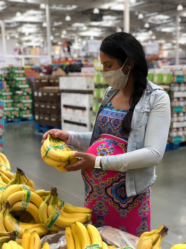 Pregnant woman at the grocery store looking at bananas.
