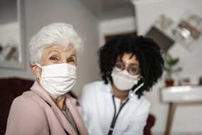 Older female patient at home with a medical provider, both wearing masks
