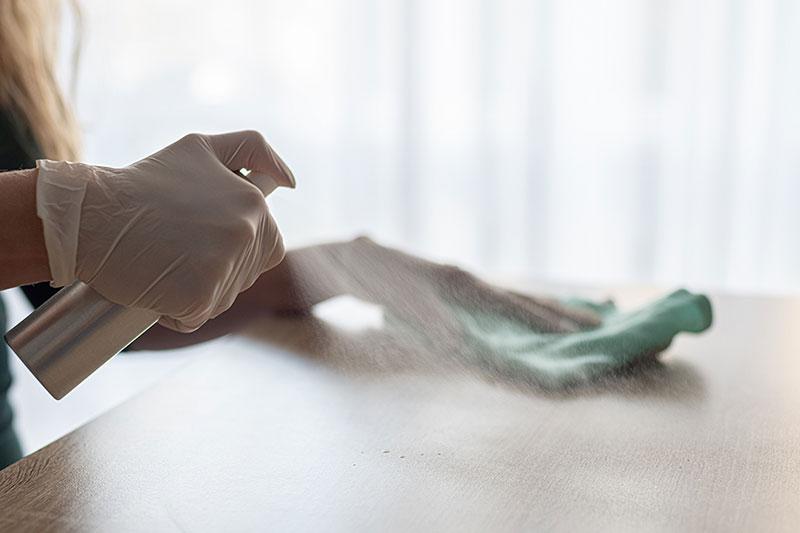 Làm vệ sinh bằng giẻ rửa bát trong khi đeo găng tay.