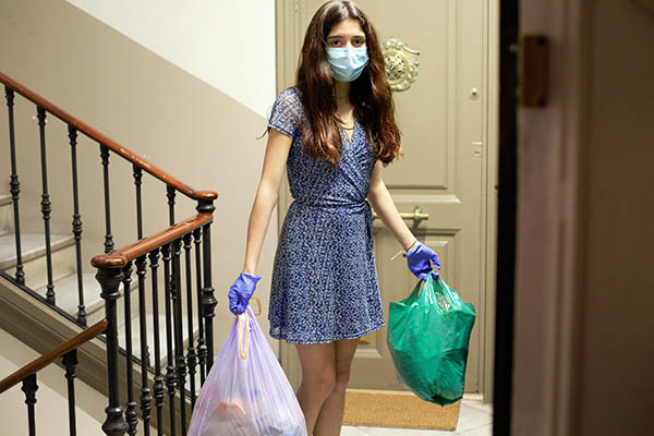 teenage girl in quarantine, wearing protective mask and gloves, in her hands she carries two garbage bags