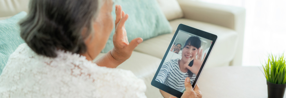 woman waving during a video chat with younger woman
