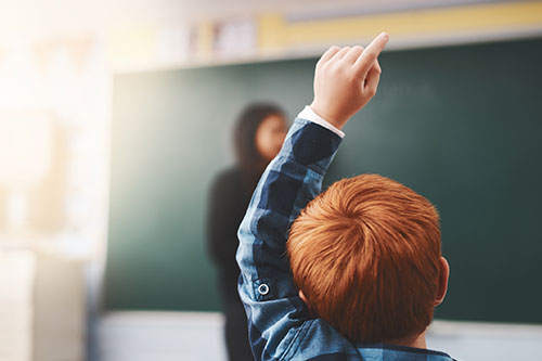 Red-headed child raising his hand in class