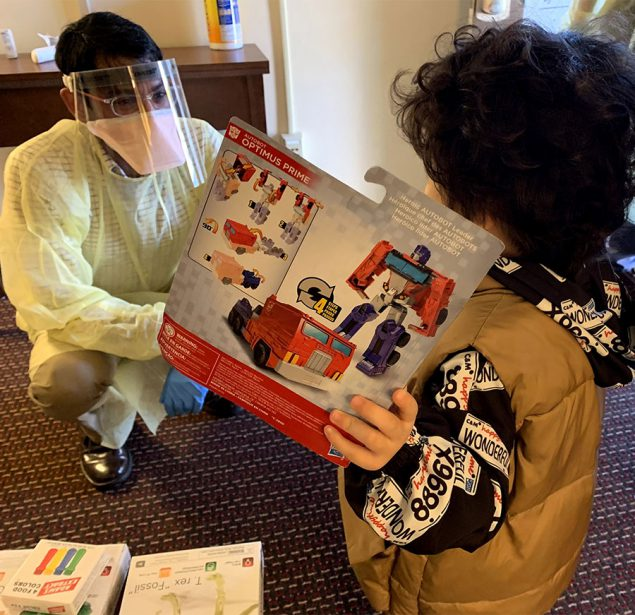 A medical officer in PPE giving a toy to a child in quarantine
