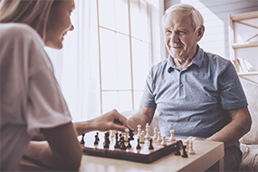 nurse playing chess with resident