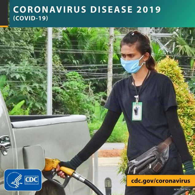Photo of a woman wearing a mask while filling her gas tank with the text CORONAVIRUS DISEASE 2019 (COVID-19), site URL, and CDC logo.