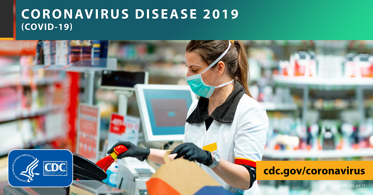 woman ringing up groceries wearing face mask and gloves with the text CORONAVIRUS DISEASE 2019 (COVID-19), cdc.gov/covid19, and CDC logo