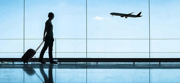 항공기를 배경으로, 여행 가방을 끌고 가는 여행자.