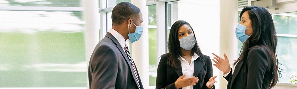 Empresarios debatiendo con las mascarillas puestas.