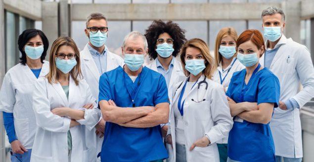 Grupo de médicos con mascarilla mirando a cámara, concepto del coronavirus.