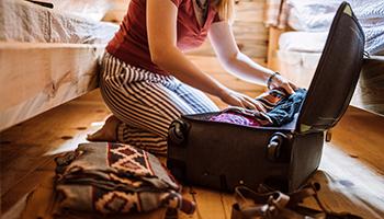 Mujer armando una maleta con ropa.