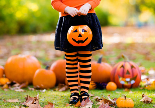 Girl in Orange and Black Tights Holding a Plastic Pumpkin