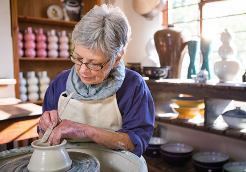 An older woman making pottery