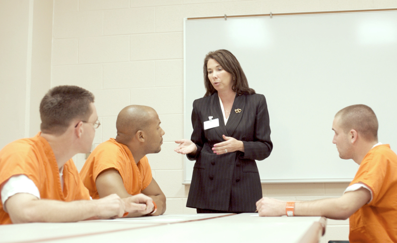 Incarcerated men listen to a correctional health provider.