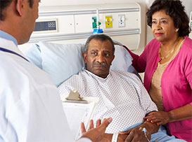 Doctor consulting with man and woman in hospital