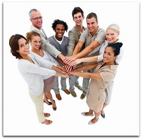 A group of people in a circle with their hands together in the middle.