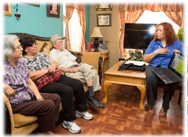 A CHW speaking to some elderly people sitting on a sofa.