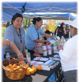 CHWs handing out healthy fruit to people at an outdoor event.