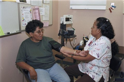 Photo of an Alaska Native woman having her blood pressure taken by a nurse.