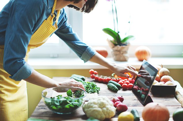 Woman cooking with fresh vegetables.