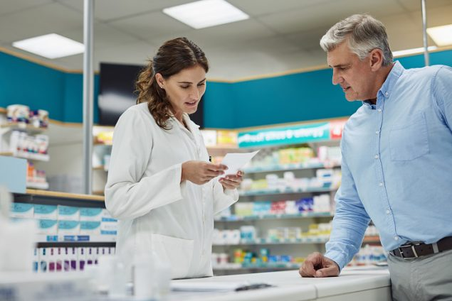 Pharmacist reviewing a prescription for customer.