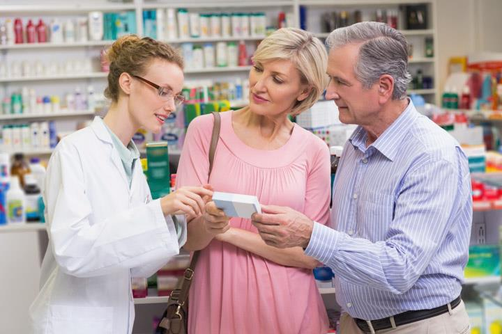 A pharmacist talking to two customers about a medication.