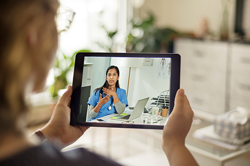 Woman holding a tablet during a video call.
