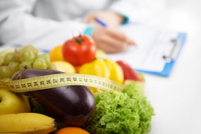 Doctor dietitian writing, closeup of fruits, vegetables and tape measure