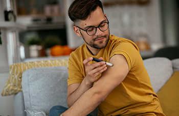 man on couch using insulin pen