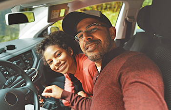 man and his daughter smiling in a car