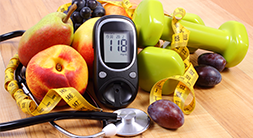 fruit, a diabetes monitor, weights and a tape measure