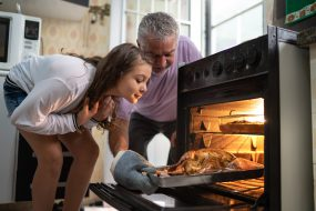Grandfather and granddaughter check turkey in the oven