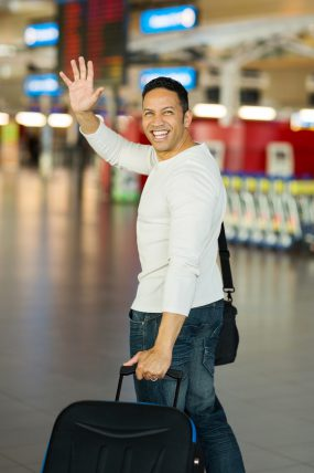 man waving goodbye at airport