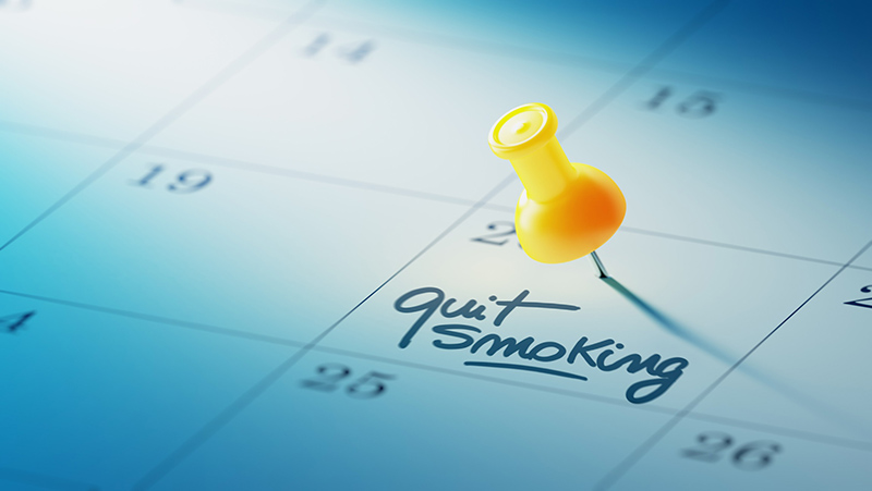 Calendar with yellow pin and 'quit smoking' written as reminder.