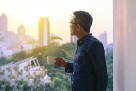 Asian man holding cup of tea and looking out a window