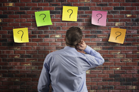 Man staring at brick wall with five question marks on it