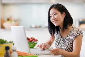 Woman looking at laptop next to a bowl of fruit