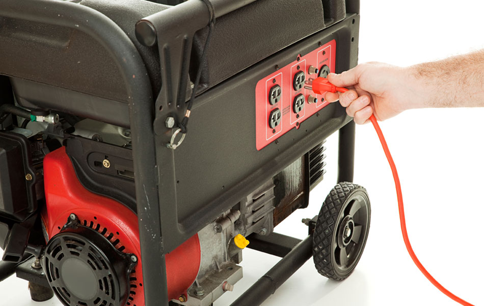 person plugging an extension cord into a portable generator