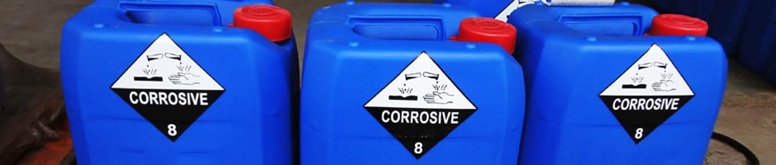 Three bright blue chemical containers for corrosive liquids with warning labels