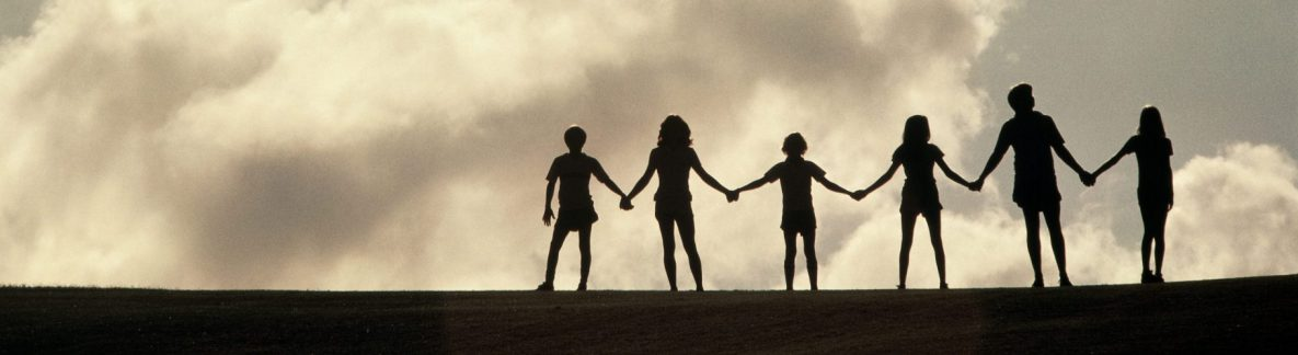 silhouette of family holding hands on top of a hill