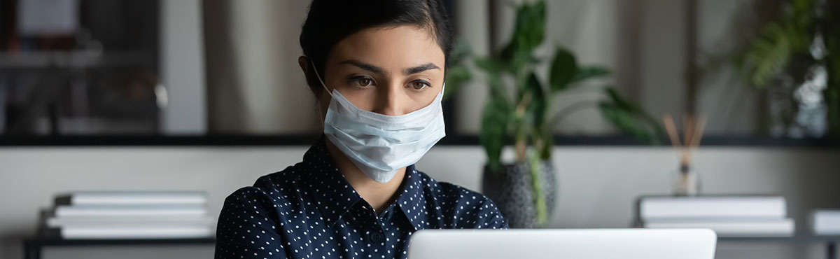Woman wearing a mask while she works on the computer in an office setting.