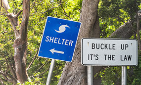 A road sign with an arrow pointing the way to a hurricane shelter