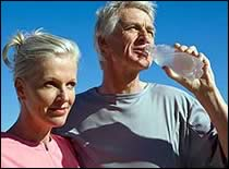 Older adult couple drinking water outside.