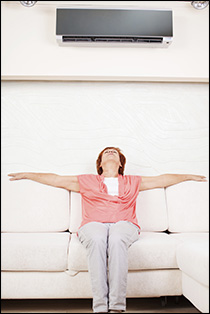 A woman sitting on a couch under an air conditioner, enjoying the cool breeze