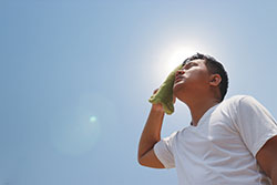 A man in the hot sun wipes the sweat from is forehead with a towel.