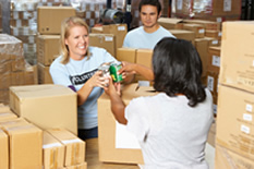 Photo of volunteers collecting food donations in warehouse.