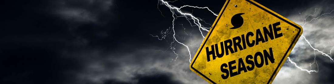 A yellow Highway caution sigh that says HURRICANE SEASON with lightning and dark sky behind it.