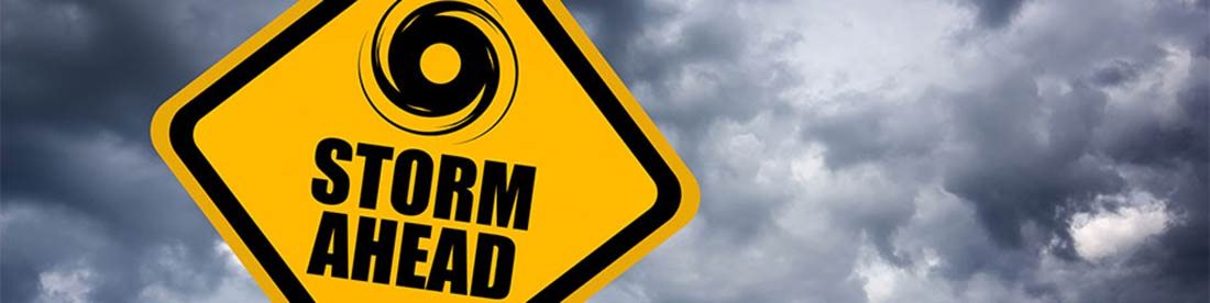 A yellow road sign with dark clouds behind it and an icon of a hurricane and words